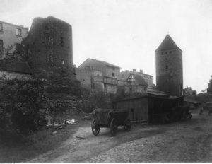 Chojnice. Fragment murów obronnych z bramą Człuchowską. Widoczne wozy wypełnione drewnem - źródło: Narodowe Archiwum Cyfrowe